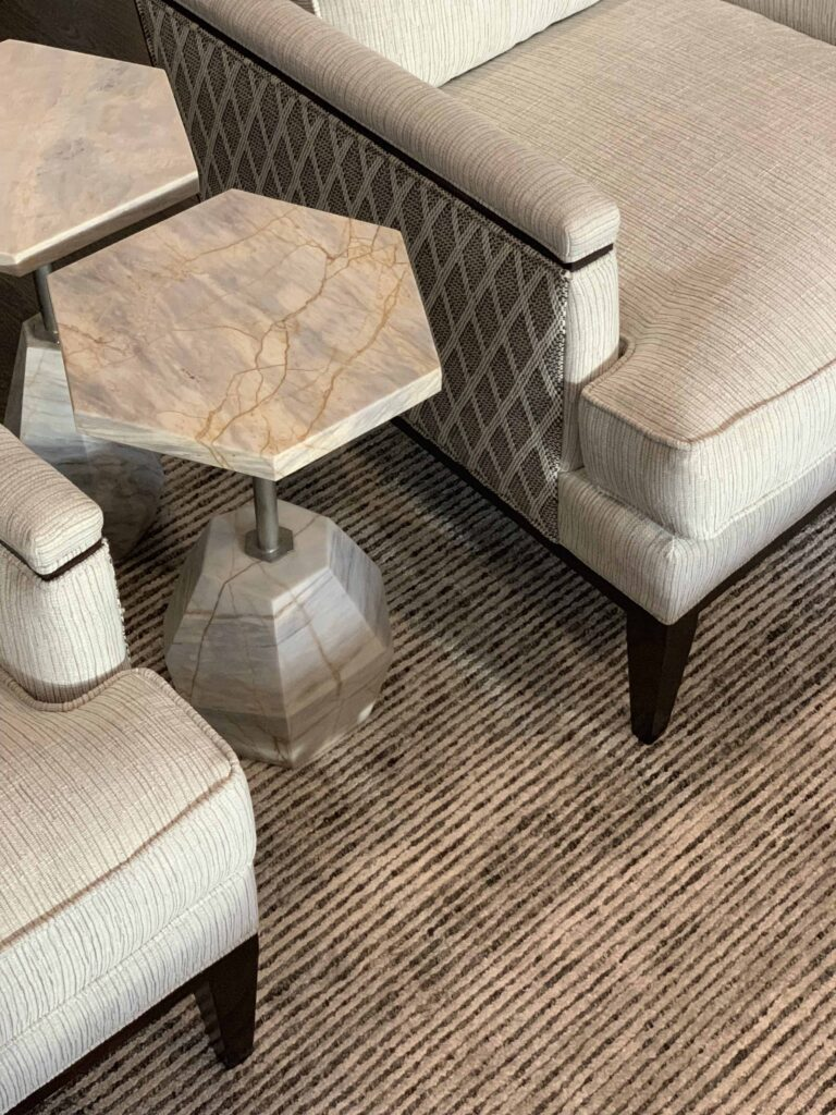 Detail shot of custom club chairs with marble side tables and textured rug.